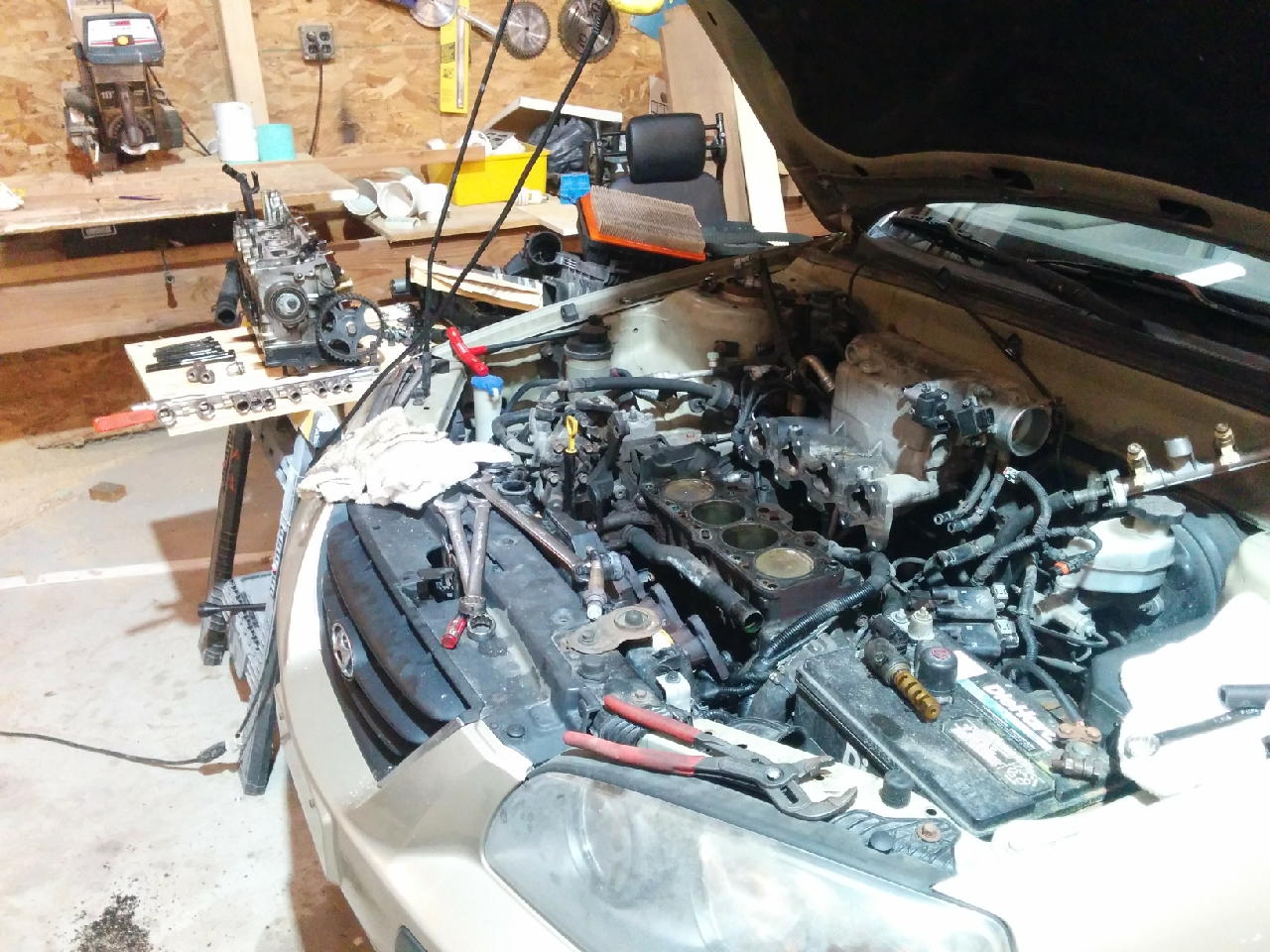 My car with the engine head removed, exposing the pistons in the combustion chambers.